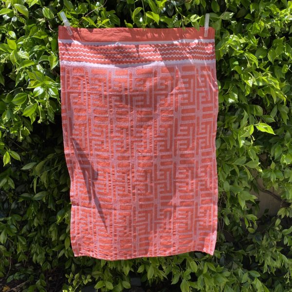 Red Kuba towel hanging in front of a bush