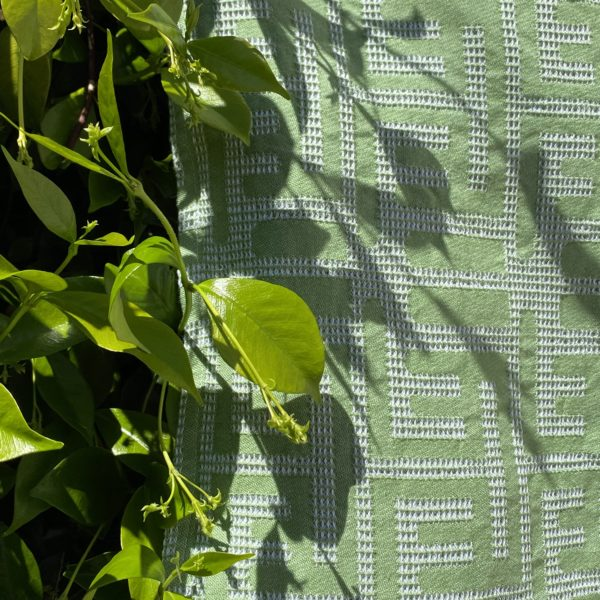 Grass green Kuba towel hanging in front of a bush