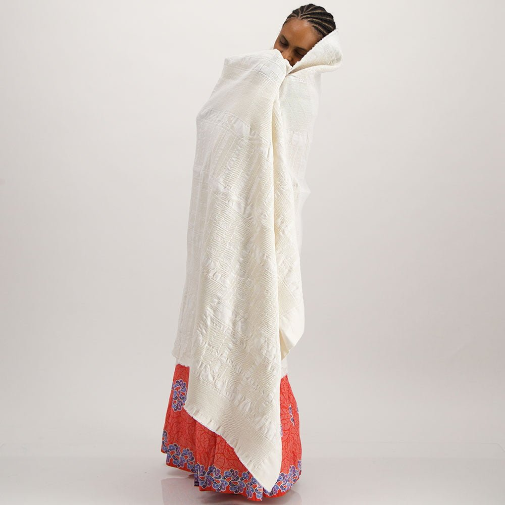 Woman in red dress wrapped in white cotton throw with jacquard woven African Bogolan pattern
