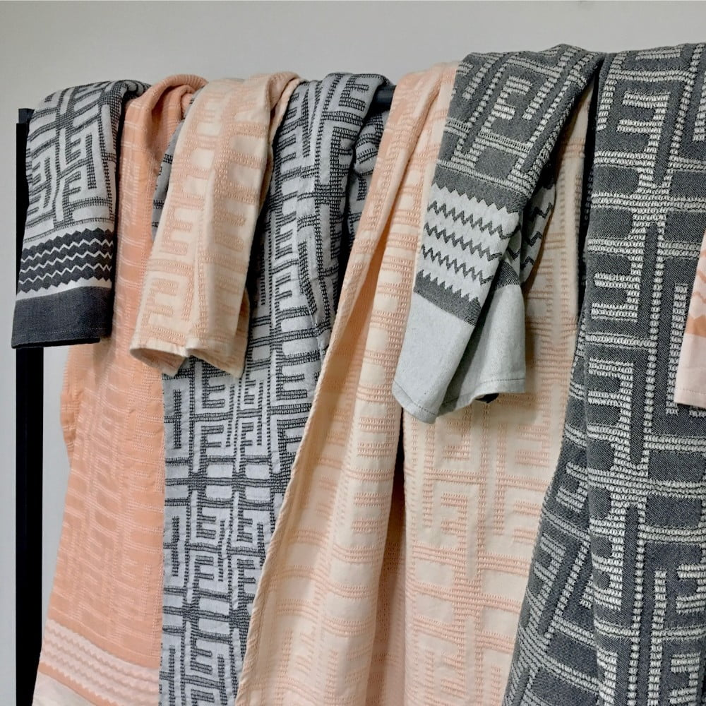 Cloth rack covered with cotton towels in shades of black and nude jacquard woven with African ethnic Kuba pattern