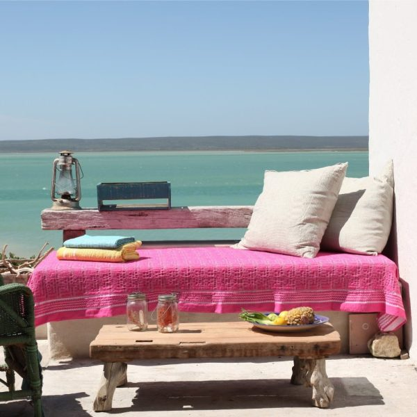 wooden bench on sea terrace draped with a pink cotton throw with jacquard woven African ethnic Kuba pattern