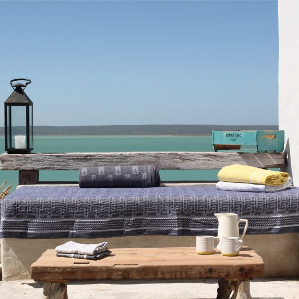 wooden bench on sea terrace draped with a blue cotton throw with jacquard woven ethnic pattern