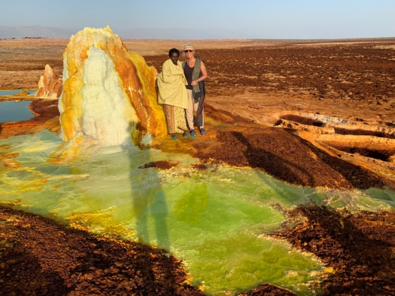 Man and woman wearing chartreuse and rust throws next to an Ethiopian Geyser in the same colors