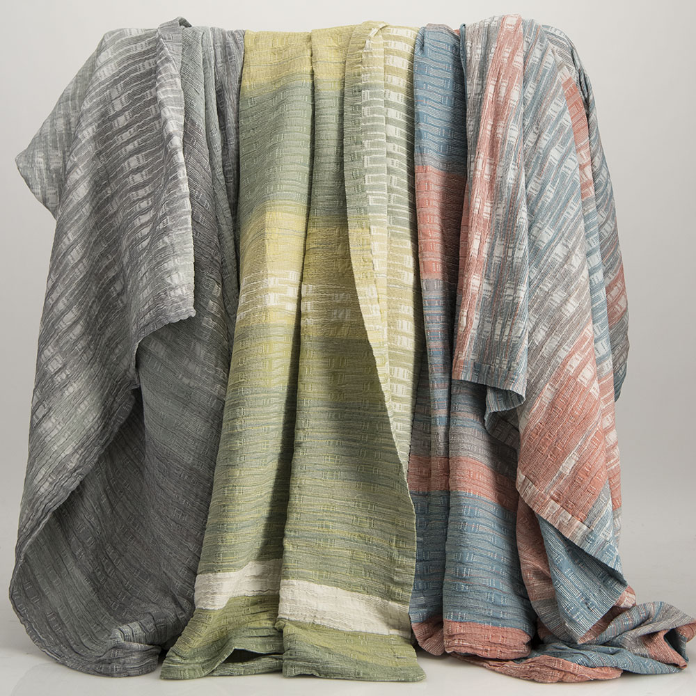 three customized bedspreads in gray, green and pink/blue hanging on a rack.