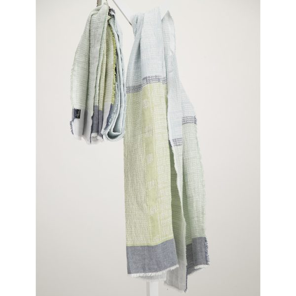 Agate light blue and green linen bogowrap scarf hanged on a coat rack