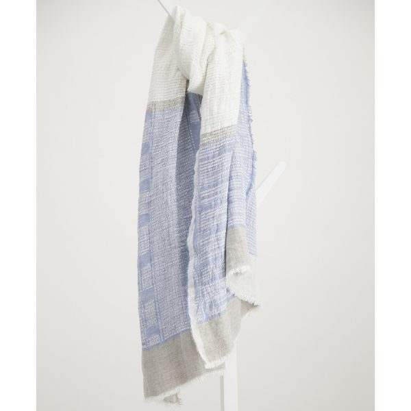 Light blue and white bogowrap linen scarf hanged on a coat rack