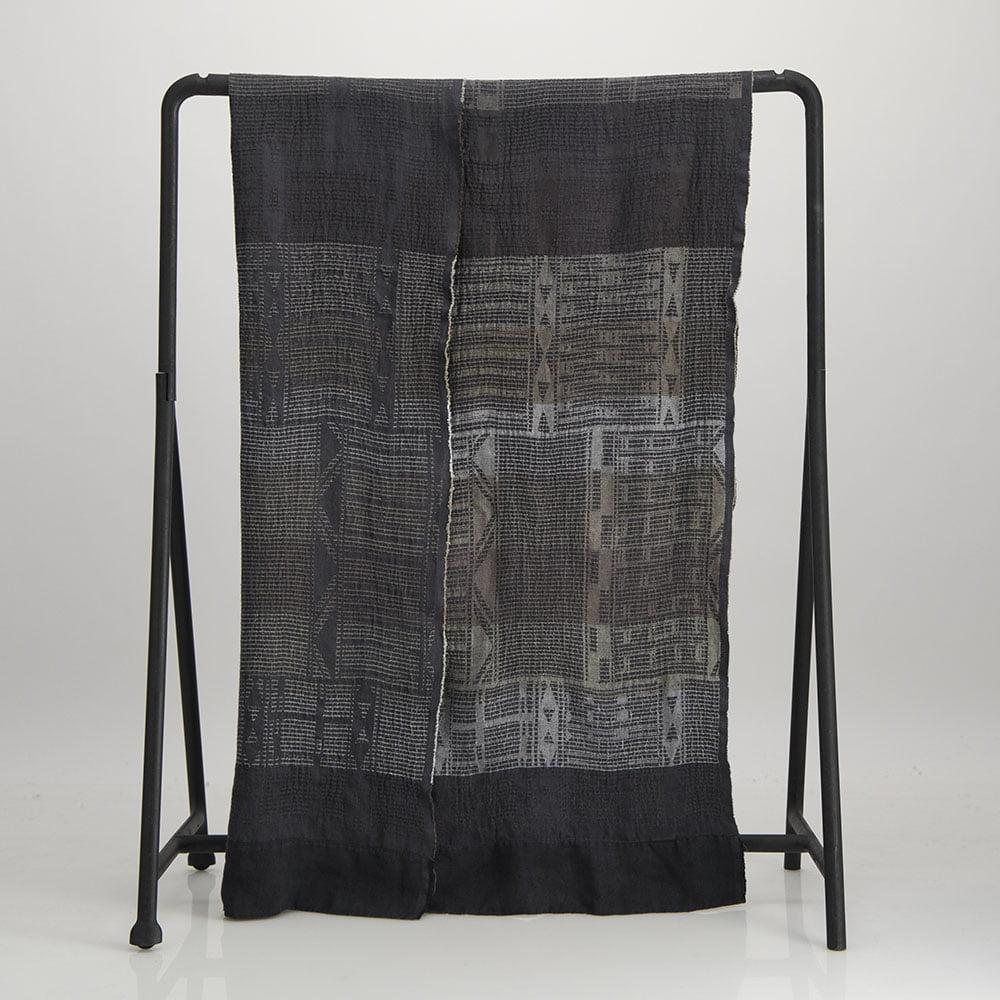 Metallic linen Bogolan throw folded and hanged over cloth rack