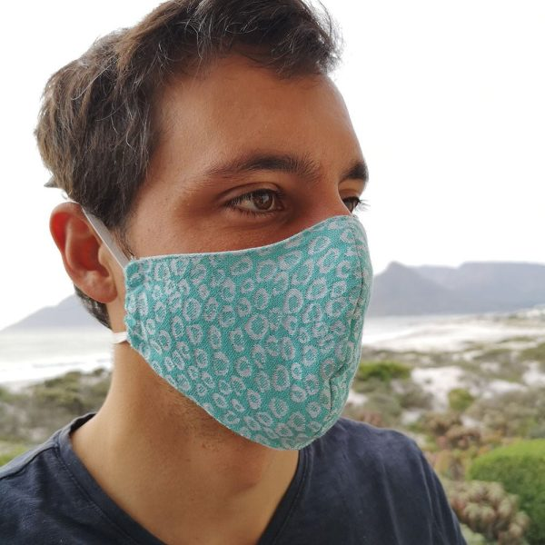 a man wearing a fabric face mask with tie back elastics, jacquard woven with turquoise and white pattern.