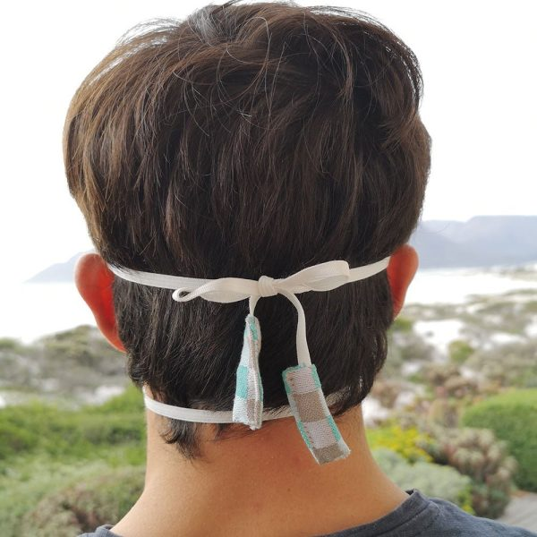 The back of the head of a man wearing a fabric face mask with tie back elastics