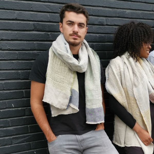 Man wearing light blue and green linen scarf with jacquard woven, intricate African pattern