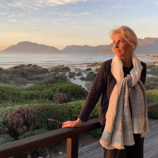 Woman wearing a navy and white linen scarf in front of a South African sea view