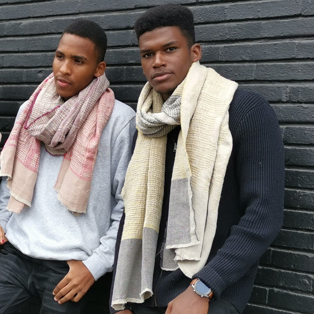 Two men leaned against a black wall wearing linen scarves with jacquard woven, intricate African pattern