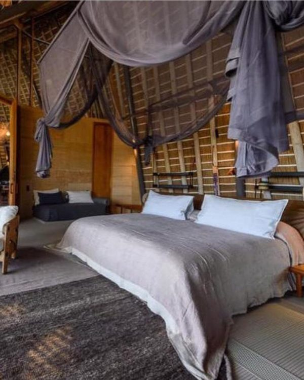 Pale purple linen bedspread on a bed in a luxury safari lodge