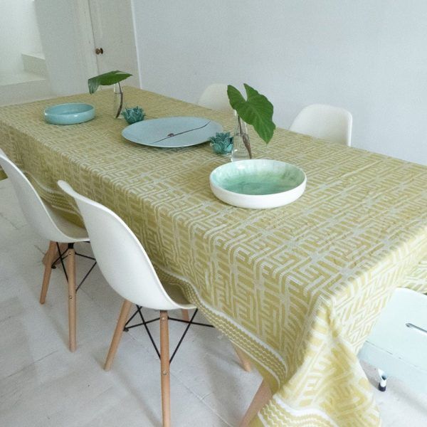 Table with chartreuse tablecloth, Jacquard woven with African ethnic Kuba pattern