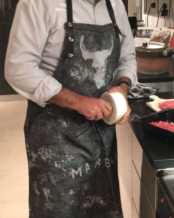 Man wearing a black and gray marbled apron with Marble Black logo
