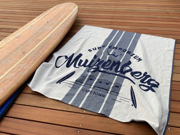Customized white beach towel with marine blue Surf shop logo next to surfboard on wooden deck