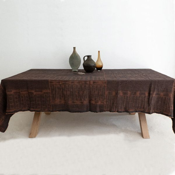 wooden table with linen tablecloth in rust with jacquard woven African Bogolan pattern