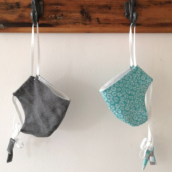 A grey and a turquoise jacquard woven fabric face mask, each hanging on a wood and metal wall hook