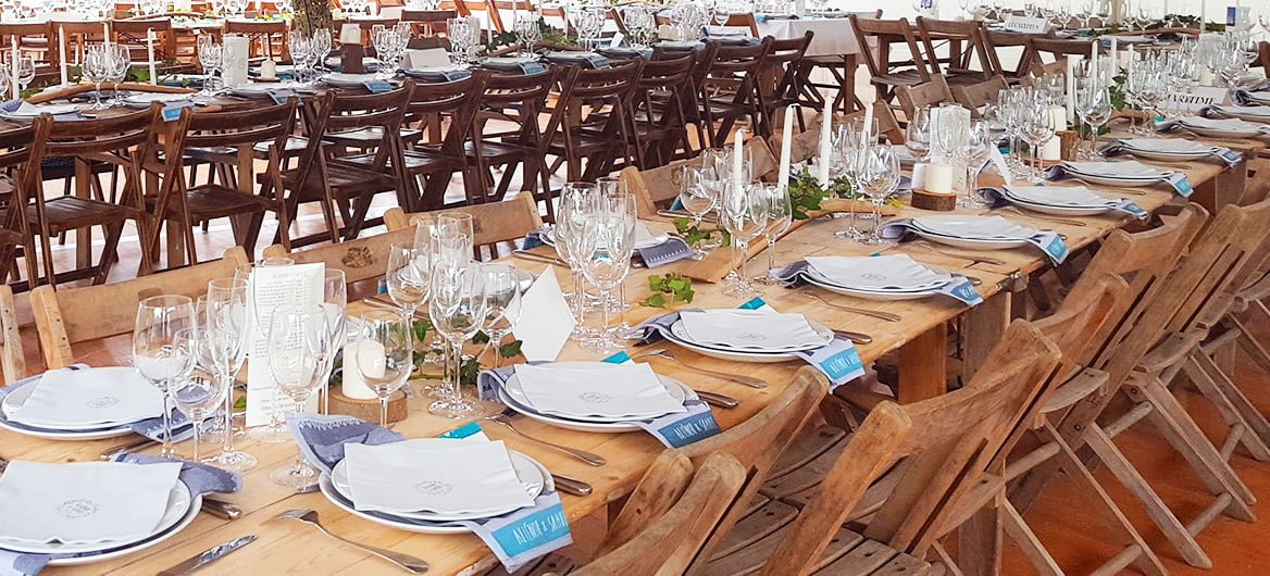 Wooden tables decorated for a wedding with customized tea towels as wedding favors for the guests