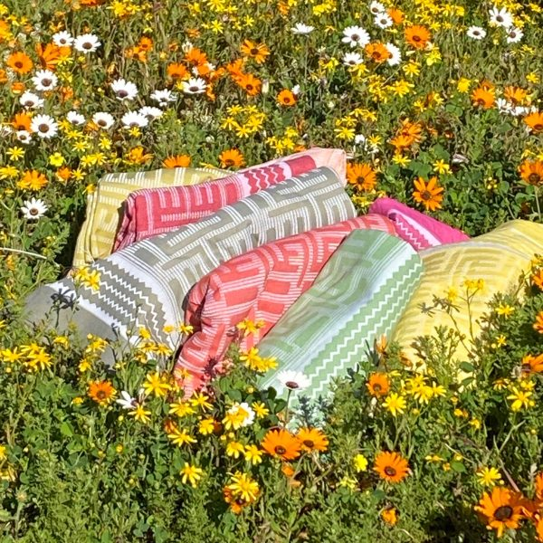 Rolled up beach towels in flowers and grass