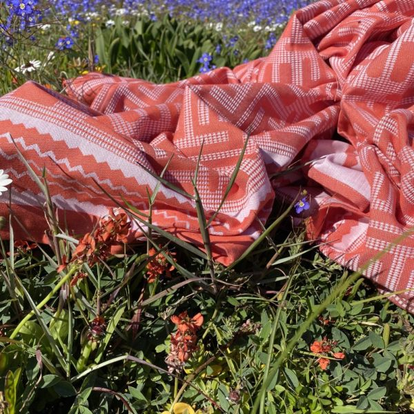 A green towel in the grass with flowers