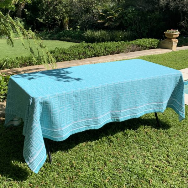 a table with a turquoise tablecloth in a garden next to a pool