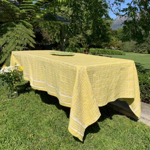 A table with a yellow table cloth in a garden in cape town