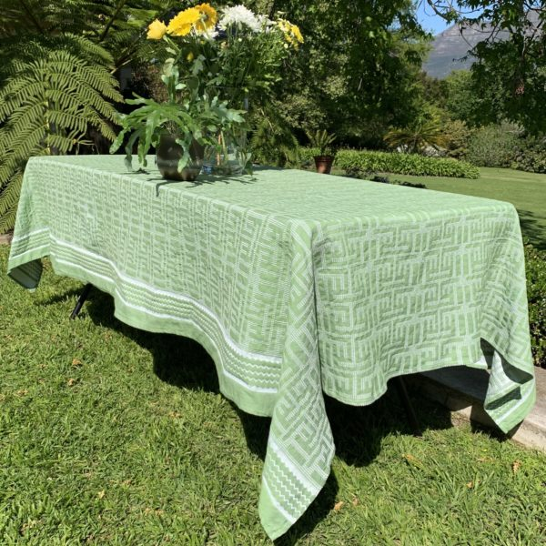 a table with a green tablecloth in a garden with flowers