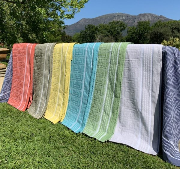 A rainbow of Kuba Cotton throws layed in front of Cape Town Mountain scenary